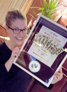 Inhaberin Eva Deuter mit der Siegerurkunde, die von Hannes Dorsch, Holzbildhauermeister aus Anzing, gestaltet wurde.